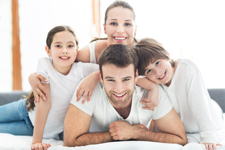 comfortable cozy: Family of four lying on bed Stock Photo