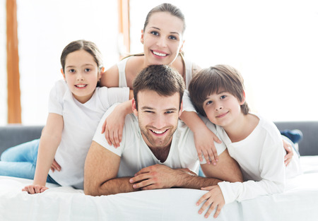Family of four lying on bed photo
