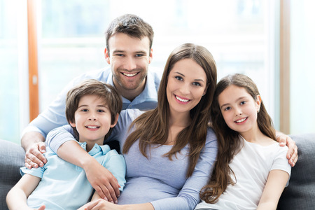 family on couch: Happy family at home Stock Photo