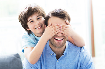 Boy covering eyes father