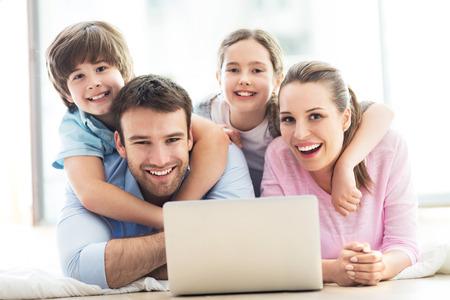 tecnología informatica: Familia feliz usando la computadora portátil junto