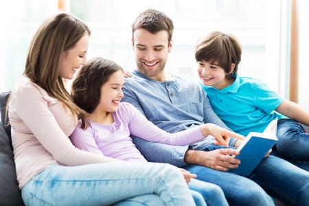 család: Boldog család olvasási könyvet együtt Stock fotó