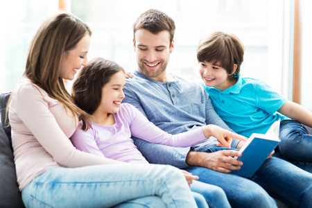 Happy family reading book together Stock Photo - 40908279