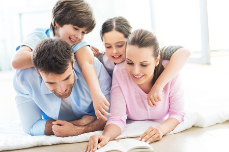 family with two children: Happy family reading book together