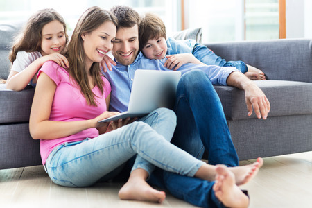 woman on couch: Family using a laptop at home