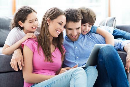 happy family: Familia usando una computadora port�til en casa Foto de archivo