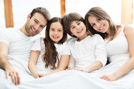 Smiling family in bed photo
