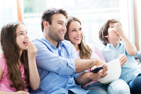 family indoors: Family watching TV and eating popcorn Stock Photo