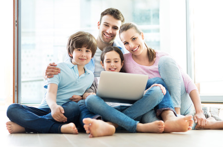 2 people: Family using a laptop at home