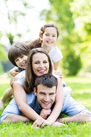 ni�as sonriendo: Familia de cuatro en el parque