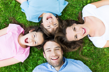 Familie liggend op gras