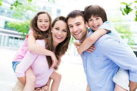 padres e hijos felices: Padres que dan a niños llevan a cuestas paseo