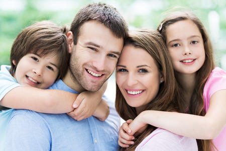 family with two children: Parents giving kids piggyback ride