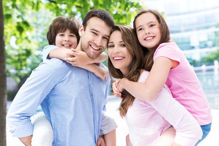 padre e hija: Padres que dan a niños llevan a cuestas paseo