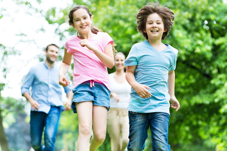 family with two children: Family running in the park