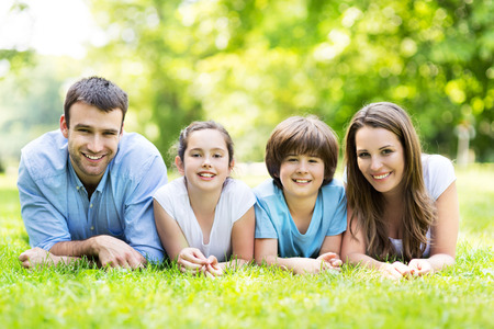 Family outdoors lying on grass Stock Photo