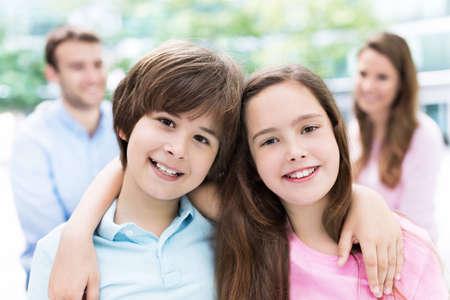 Kinderen lachend met hun ouders op de achtergrond