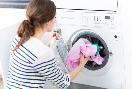 Woman loading washing machine Stok Fotoğraf - 41796599