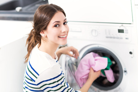 laundry: Mujer lavadora de carga Foto de archivo