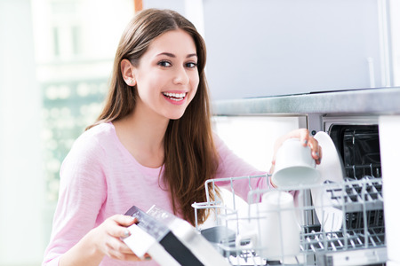 Woman loading dishwasher Standard-Bild