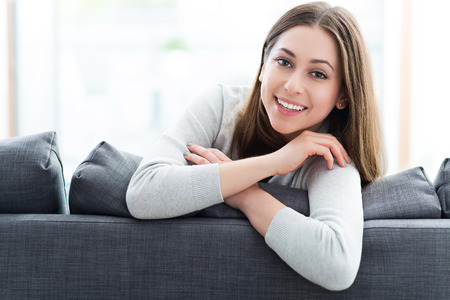 domestic life: Woman relaxing on sofa