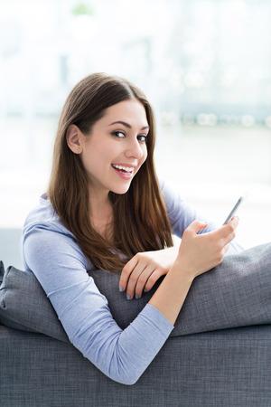 using phone: Woman using mobile phone on sofa