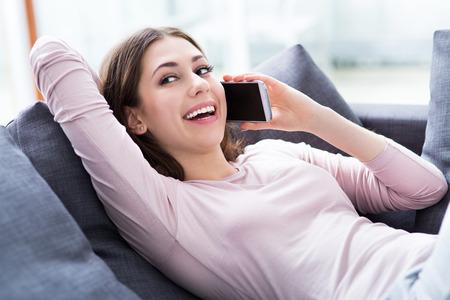 Woman using mobile phone on sofa