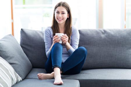 descansando: Mujer de tomar café en el sofá