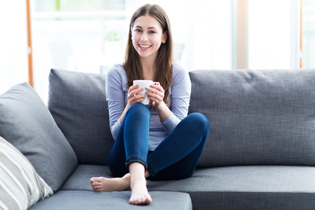 woman couch: Woman drinking coffee on sofa