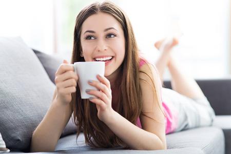 tomando café: Mujer de tomar café en el sofá