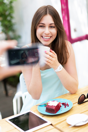 taking photo: Man taking photo of his girlfriend at outdoor cafe Stock Photo