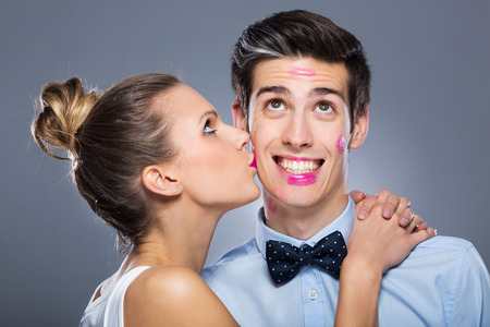 lipstick kiss: Young woman kissing man Stock Photo