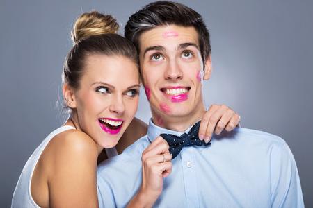 lipstick: Hombre con marcas de lápiz labial y mujer sonriente Foto de archivo