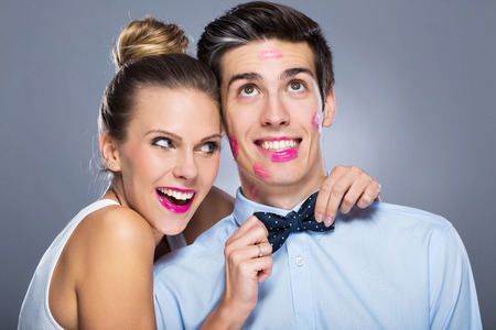 Man with lipstick marks and smiling woman Stock Photo