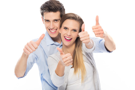happy people white background: Young couple showing thumbs up Stock Photo