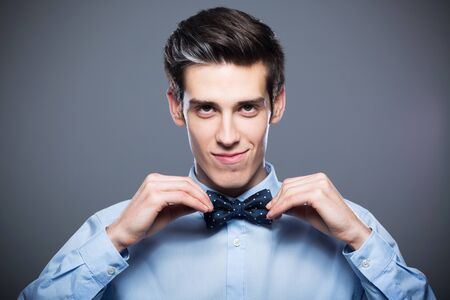 adjusting: Man adjusting bow tie