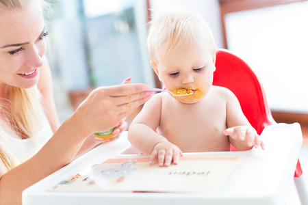 high chair: Mother feeding baby with spoon Stock Photo
