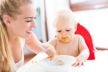 spoons: Mother feeding baby with spoon Stock Photo