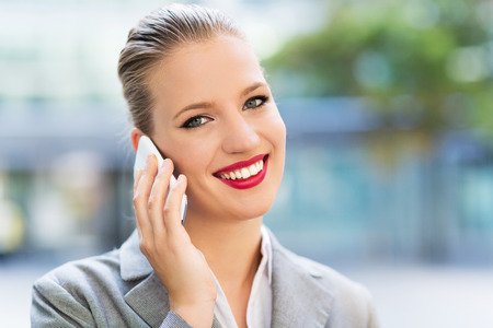 smiling: Businesswoman using mobile phone