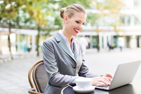 outdoor cafe: Businesswoman using a laptop at a cafe