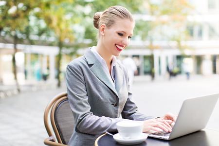 cafe internet: Empresaria que usa un ordenador portátil en un café