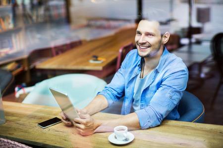 ebook: Man using digital tablet at cafe