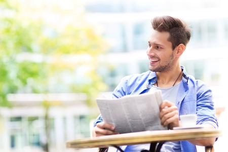 Man het lezen van de krant op een terrasje Stockfoto