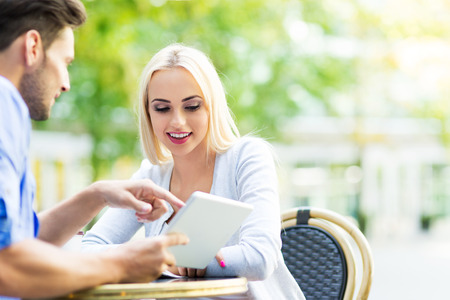 couple outdoor: Couple using digital tablet at cafe