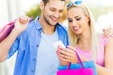 man and woman with shopping bags: Young people using smartphone