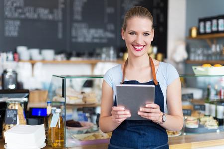 Trotse jonge vrouwelijke cafe eigenaar