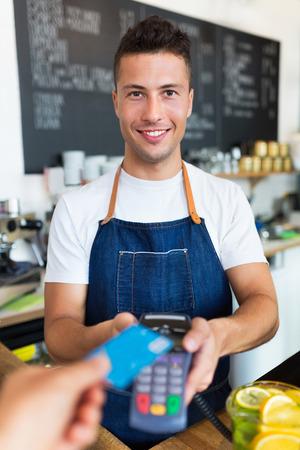 holding credit card: Man holding credit card reader at cafe