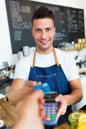 restaurant people: Man holding credit card reader at cafe