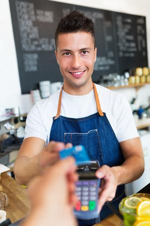 Man met credit card reader in cafe Stockfoto