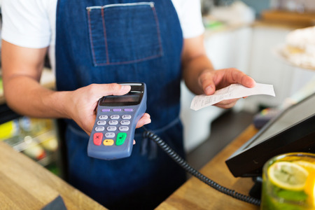 overdraft: Waiter holding a credit card reader